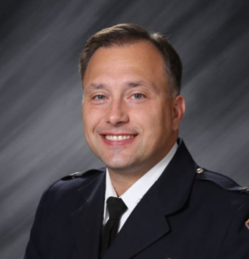 Photograph (headshot) of Chief Bailey with simple grey background.