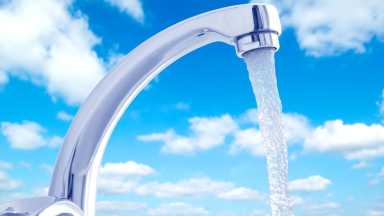 Water flowing from the faucet against the blue sky