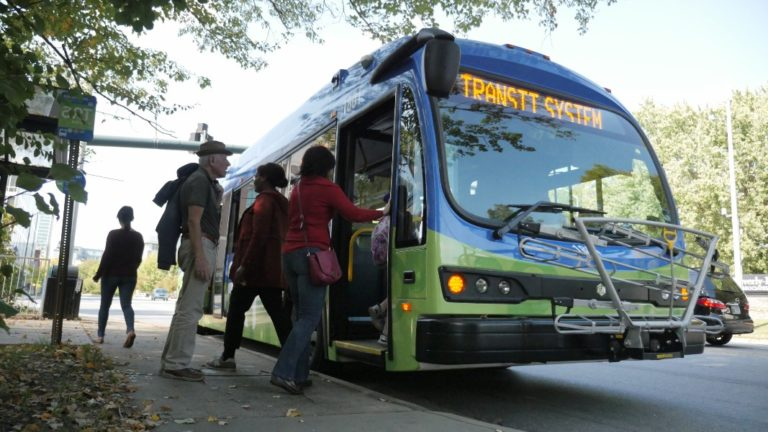 art transit bus taking on bus riders at a stop