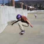 A young man skateboarding at the skate park