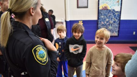 asheville police officer talking with young students