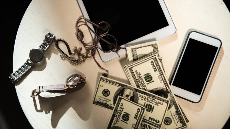 valuables of electronics and jewelry and money on tables