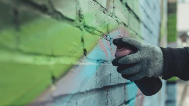 graffiti being sprayed on wall