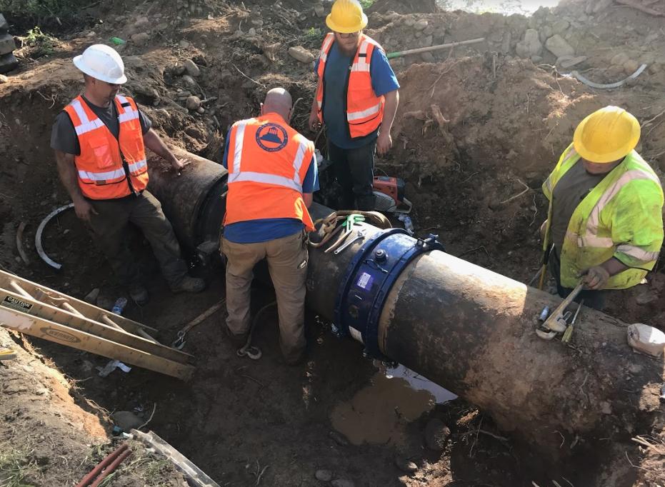 Image of an Asheville Water Maintenance crew working to repair a broken waterline on Bee Tree Creek.