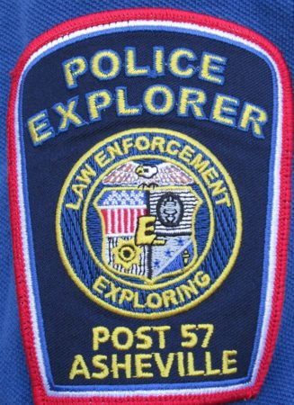 "Photograph of the APD explorer post patch. At the top says""Police Explorer"", the middle is the law enforcement exploring seal, and ""Post 57 Asheville"" text at the bottom."