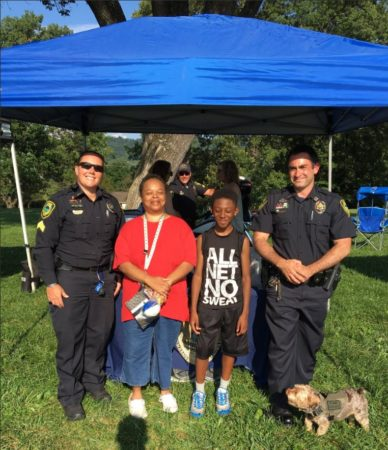 Two uniformed police officers pose with two community members and a small dog near a tent in Aston Park in Asheville.