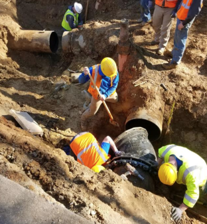 workers in ditch with large water pipes