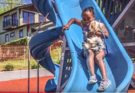 girl coming down slide at park
