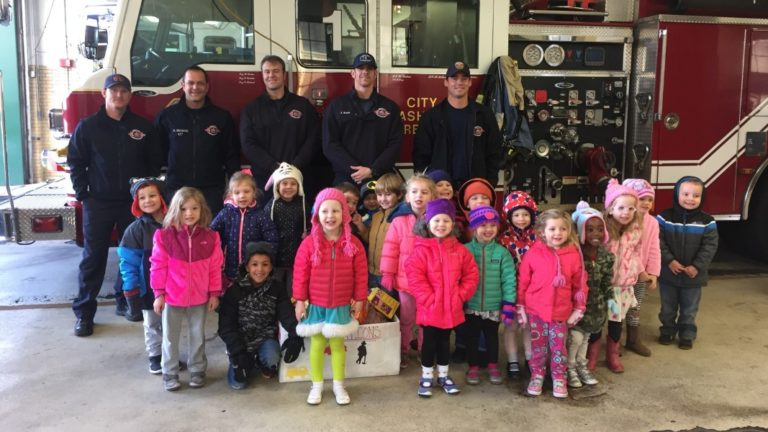 firemen posing with children in front of firetruck