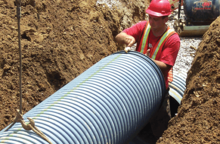 Photo of large pipe being installed in ditch