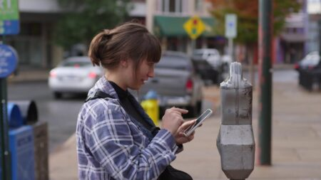 Person using cellphone in front of parking meter