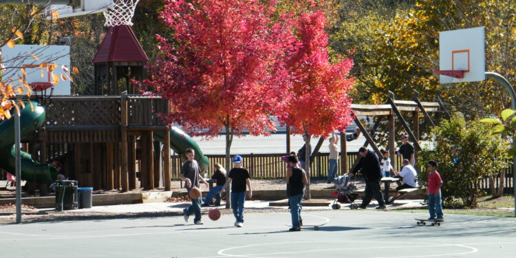 children playing on basketball court in fall